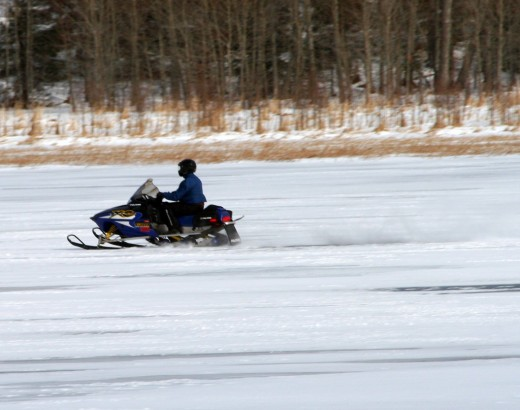 Snowmobile rider driving across a frozen lake.