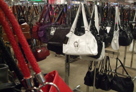 Rows of handbags in a retail store.