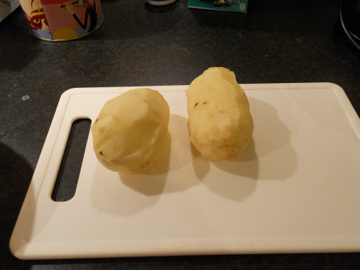 Using a potato peeler, remove the skin from two potatoes.