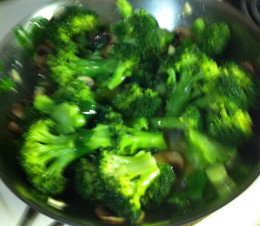 Frying broccoli, green onions, mushrooms, and garlic in olive oil.