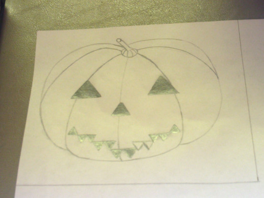 Draw a jack-o'-lantern on a sheet of paper.