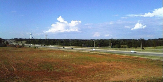 Blue sky with fluffy white clouds over red dirt.  Red, white and blue are true adjectives describing Oklahoma.  Photo taken of I-35 going north from Edmond, looking toward Highway 66 to Arcadia Red Barn and POPS.