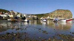 Staithes Harbour from the south-east with Cat Nab (right). The shop where James Cook first worked was wrecked in a freak storm in the late 18th Century. The hill cracked in two. Harbour debris stems from then and a later 19th Century freak storm