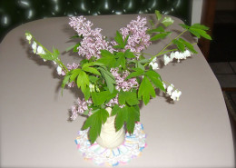 Lilacs and white Bleeding Heart create an airy bouquet for spring time.  I anchor it a bit with a solid vase and a round doily.