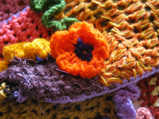 Orange Crochet Flower Closeup Jprescott DESCRIPTIONCloseup of an orange crocheted flower with a multi-colored crochet fabric background.