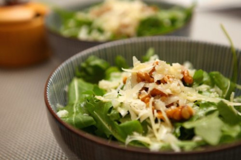 A simple green salad with arugula, grana padano, and walnuts.