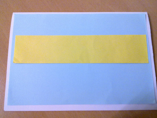 Paste the yellow strip on top the blue paper