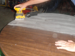 Using an electric sander to prepare the surface of the table for the chalkboard paint