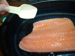 A drizzle of canola oil helps the crust adhere to the salmon fillet.