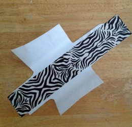 Applying the zebra print tape to the back of the prepared wrapper.