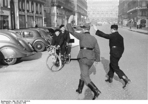 German soldiers hailing a tandem bicycle powered taxicab in occupied Paris, December 1st 1940. The building visible at the end of the street is Palais Garnier, Paris Opera House
