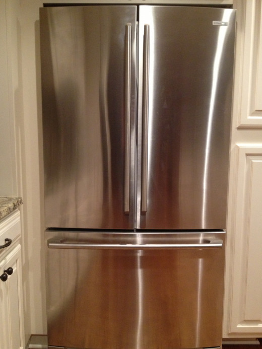 I use microfiber cloths with water to wipe my kids finger prints off the fridge.  It is cost easy and effective.