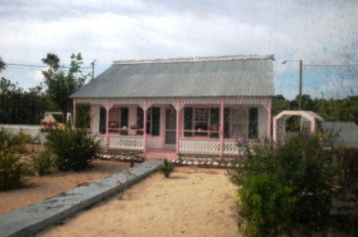 The Pink House. Said to be the second oldest house on the Grand Cayman Island. And, no it's not raining dust. The dusty effect to the right of the image is from taking this shot through the buse's window. Use image by permission only.