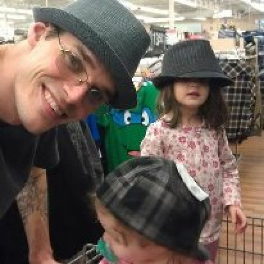 My son and his two girls, my granddaugthers, goofing off at the mall trying on appropriate hats?