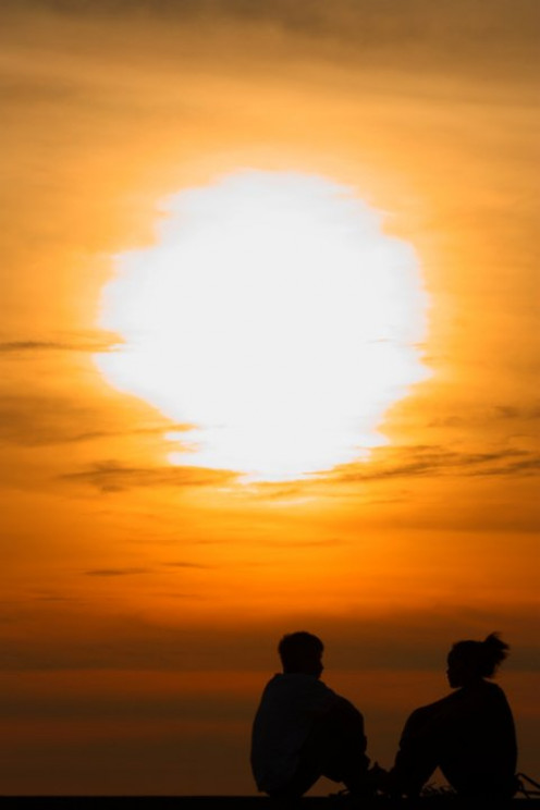 Sunset with silhouette of boy and girl.