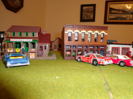 These buildings have not been weathered yet.  The three vehicles in this photo have been weathered to look more realistic.