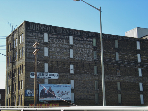 An old warehouse building in Bloomington, Illinois has signs advertising multitude of defunct products and services.
