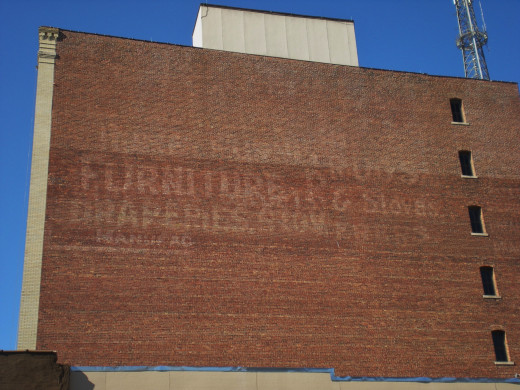 Fading advertising touting furniture and stoves on a building in Downtown Bloomington.