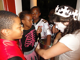 Halloween in Mid-City New Orleans. Xy lets the neighbor kids take a reach in her candy pot.