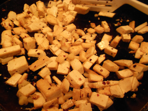 Add red pepper flakes, stir and turn the tofu until browned.