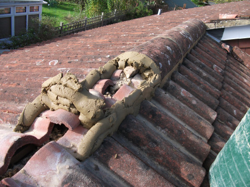 Cement being laid to roof, note that the ridge tile is bedded down onto the cement.