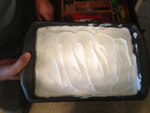 Once cake has called, spread thin layer of Cool Whip