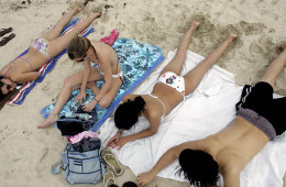 Young people sunbathing with bathing suits on in the sunlight.