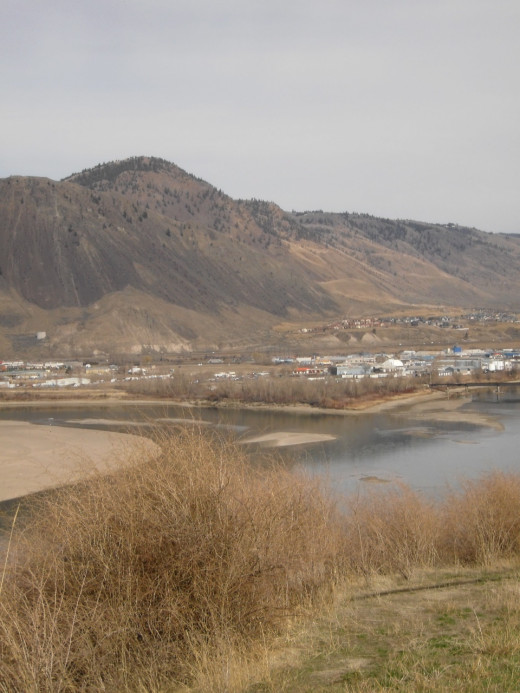 "Confluence of North and South Thompson Rivers in the hot grassland valley at Kamloops, which takes its name from ""Tk'emlups"" in the Secwepemc language, meaning ""meeting waters.""  The northern river is clearer blue, while the southern.one is pale."