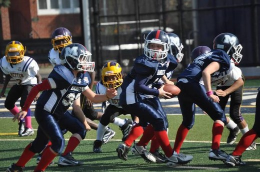 Shane Steinlauf looks to handoff to one of his Manhattan Bandits running backs.