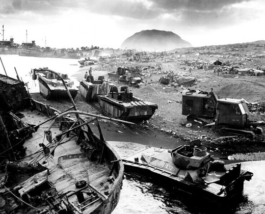 U.S. amtracs and other mobile vehicles lay smashed by Japanese mortar and artillery fire and/or caught in the black sand.