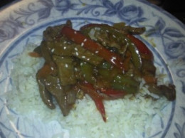 Beef and veggie stir fry served over a bed of rice.