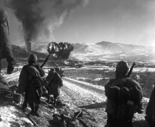 U.S. Marines move forward after close-air support flushes out the enemy from hillside trenches.