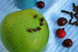 Piercing the fruit first makes inserting the cloves easier.