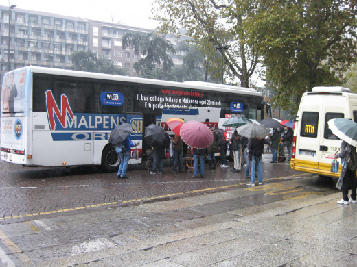 Shuttle bus dropping off passengers outside Milan Central station (Milano Centrale).