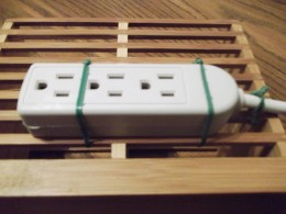 Attach small power strip to lower back of kitchen utensil container.  As the picture illustrates, one with openings works well.