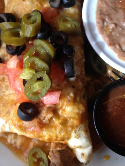 Chicken burrito, garnished with jalapanos, tomatoes, black olives; a side of refried beans with cheese