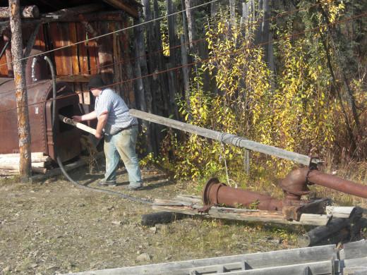 Miner demonstrating gold mining equipment.
