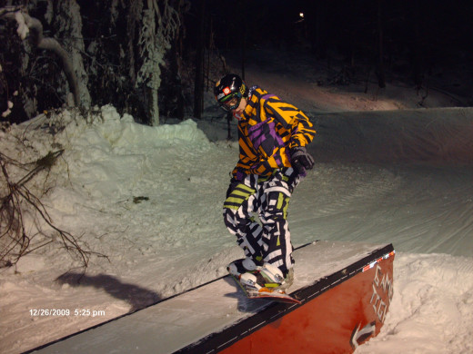 A snowboarder practicing jibbing