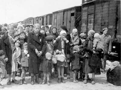 Arrested Jews were transported by train from Paris to the concentration camps. This picture  probably shows the arrival at the camp, as one person on the right is wearing the striped camp uniform. The number of visible children is appalling.