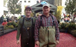 Two Ocean Spray cranberry workers standing in middle of cranberry bog.