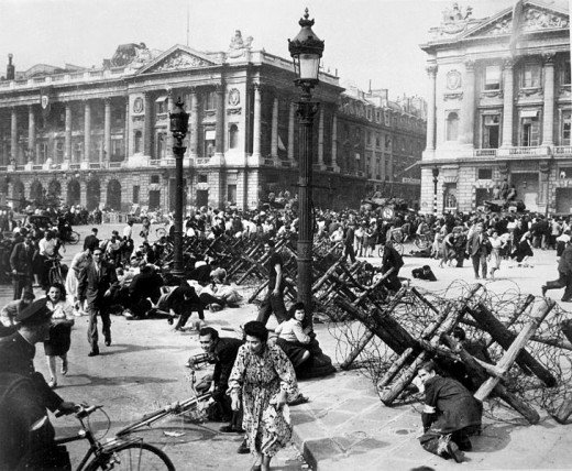 Crowds of Parisians celebrating the entry of Allied troops into Paris scatter for cover as a sniper fires from a building on the place De La Concorde. Although the Germans surrendered the city, small bands of snipers still remained. August 26 1944.