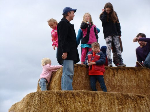 The kids climbed the huge straw mountain.