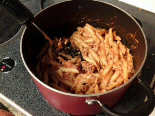 Mixing the turkey,pasta, and sauce together