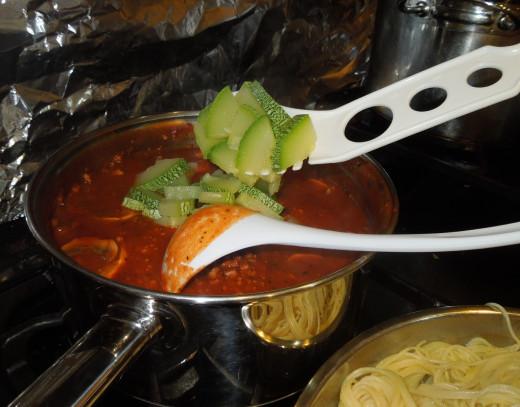 Adding in the zucchini to the spaghetti sauce