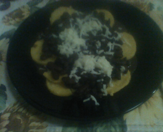 A serving of polenta cakes topped with the bean mix and shredded cheese.