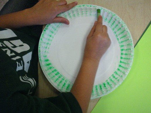 Coloring the outer circle of the plate.