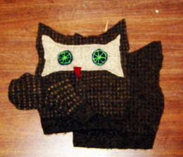 The embroidered eyes, red beak, and mask are are attached to the front of the owl before sewing it together
