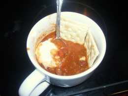 Half-eaten bowl of chili with crackers and sour cream