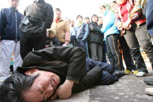 Bystanders in China watch as a man suffers a heart attack on the street.