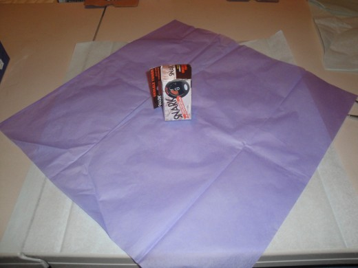 Place 2-3 pieces of tissue paper caddy-corner to each other.  Place gift in center of tissue paper.  For a large object, spread tissue papers out and tape where they over lap.  You want several inches more then double the size of your gift.